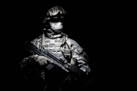 United States Armed Forces soldier in battledress with black glasses and mask on face, armed squad automatic weapon emerges from darkness. Military threat, secret stealth mission, hybrid war combatant