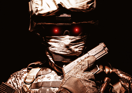 Special operations forces soldier in combat helmet with terrible burning red eyes posing with sidearm service pistol in hand. Brown tone, high contrast, cropped on black background Stock Photo