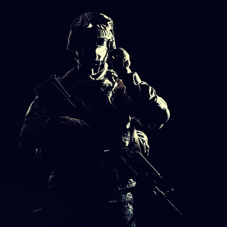 US marine raider in combat uniform with hidden face, armed with assault carbine low key, high contract studio shot on black background. Equipped army soldier standing in darkness with weapon in hands