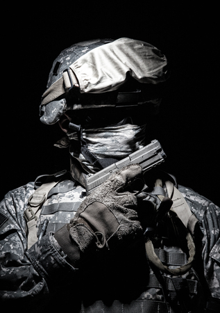 Special operations forces soldier in combat helmet with hidden behind balaclava and dark glasses face posing with sidearm service pistol in hand. Brown tone, high contrast, cropped on black background Фото со стока - 101810620