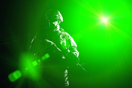 US marine raider in combat uniform with hidden face, armed with assault carbine low key, high contract studio shot on black background in blinding light. Equipped army soldier standing in darkness with weapon in hands