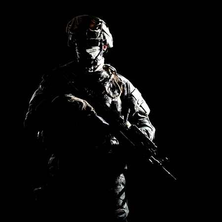 US marine raider in combat uniform with hidden face, armed with assault carbine low key, high contract studio shot on black background. Equipped army soldier standing in darkness with weapon in hands Stock Photo
