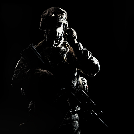 US marine raider in combat uniform with hidden face, armed with assault carbine low key, high contract studio shot on black background. Equipped army soldier standing in darkness with weapon in hands Imagens