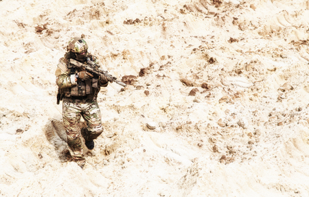 Special operations forces soldier, US army infantryman carefully sneaking, walking with service rifle in hands in hot sandy and rocky area. Military mission on Meddle East, modern warfare in desert Stock Photo
