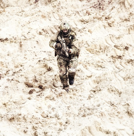 Modern infantry soldier in protective camouflage uniform, in helmet and mask, running with assault rifle in hands through hot sands, looking at camera. Military action in desert, attacking infantry