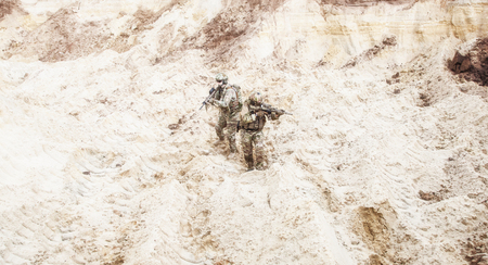 Two infantry soldiers in combat camo uniform, with tactical ammunition, carefully walking and aiming with assault rifles in unknown desert area. Military reconnaissance, scouting on enemy territory Stock Photo