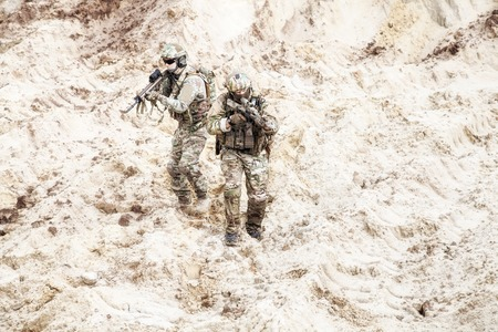 Two infantry soldiers in combat camo uniform, with tactical ammunition, carefully walking and aiming with assault rifles in unknown desert area. Military reconnaissance, scouting on enemy territory 写真素材