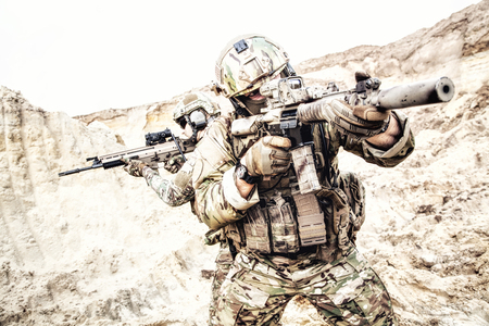 Two soldiers of special forces, american army rangers armed with assault rifles aiming in red dot collimating optics sights, searching enemies, covering and supporting each other with fire in desert