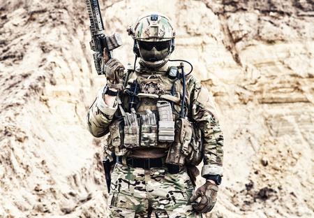 Army soldier, private military company fighter with hidden identity in battle uniform, helmet, body armor and radio headset, standing with service rifle in rocky area