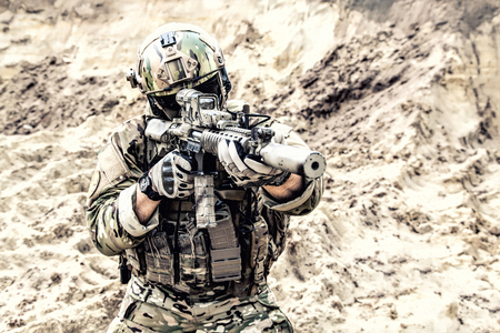 Special operations forces fighter, modern infantry soldier in full ammunition, aiming with red dot sight and shooting with assault carbine in desert area. Fire contact with enemy during war conflict