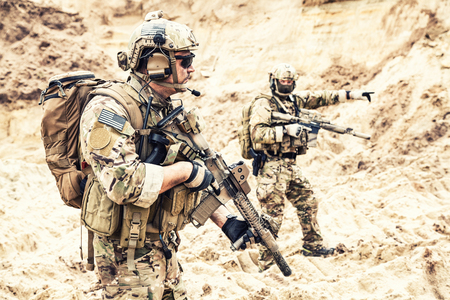 Two armed US army commandos or military scouts equipped with radio headset moving forward in sands during enemy area reconnaissance. Special forces operation, long range surveillance mission in desert