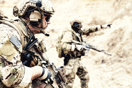 US special operations forces fighters armed with assault rifle, in opscore helmet, radio tactical ops headset, moving forward with caution in desert. Reconnaissance by fire in zone of war conflict