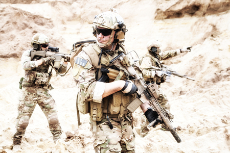 Group of well equipped US army commandos armed with assault rifles, moving through sandy terrain or desert. Military reconnaissance team secret operation, special forces mission on enemy territory Stock Photo - 104627246