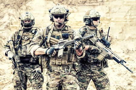 Group portrait of US army elite members, private military company servicemen, anti terrorist squad fighters standing together with guns. Brothers in arms, war conflict combatants, soldiers of fortune Standard-Bild - 104627247