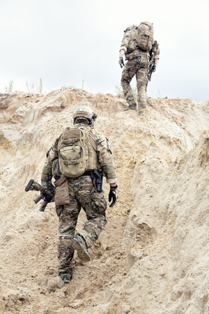 Two modern infantry, special operations forces soldiers, military intelligence specialists armed with service rifles in protective camouflage uniform with backpack on backs climbing on sand dune