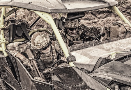 Armed modern infantry soldiers, elite members of special forces, private military company mercenaries extremely driving desert patrol vehicle while going at rough terrain. Desaturated, cropped shoot
