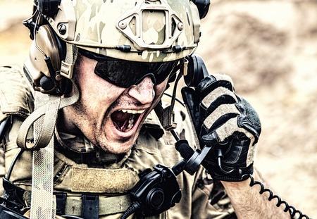 Soldat der Spezialeinheit, militärischer Kommunikationsbetreiber oder Instandhalter in Helm und Brille, der während der Schlacht in der Wüste im Radio schreit. Verstärkung abrufen, Situation auf dem Schlachtfeld melden