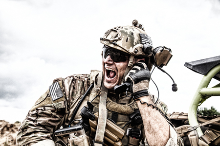 Special forces soldier, military communications operator or maintainer in helmet and glasses, screaming in radio during battle in desert. Calling up reinforcements, reporting situation on battlefield