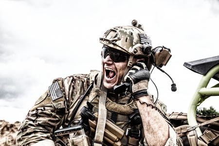 Special forces soldaat, militaire communicatie-operator of onderhouder in helm en bril, schreeuwend op de radio tijdens een gevecht in de woestijn. Oproepen van versterkingen, melding van situatie op slagveld Stockfoto