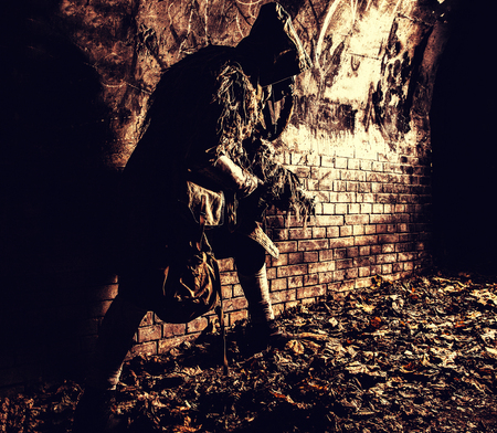 Post apocalyptic survivor, mysterious underground creature, stalker in gas mask and rags with runes, armed with handmade gun, hiding in dungeon, abandoned tunnel or city dark catacombs, sepia toned Stock Photo
