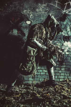 Nuclear post-apocalypse survivor in gas mask and ghillie cape, sneaking in deep underground tunnel or dark catacombs, walking in post apocalyptic city sewage collector with gun in hands, desaturated Reklamní fotografie