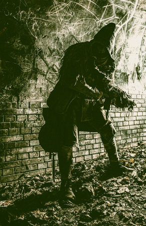 Post apocalyptic survivor, living underground mutant, wearing tattered rags hiding in deep bunker, city tunnel or catacombs, sneaking in dungeon with handmade firearm weapon, low key, toned image Stock Photo