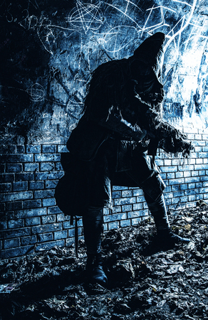 Post apocalyptic survivor, living underground mutant, wearing tattered rags hiding in deep bunker, city tunnel or catacombs, sneaking in dungeon with handmade firearm weapon, low key, blue toned image Stock Photo