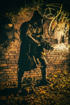 Post apocalyptic survivor, living underground mutant, wearing tattered rags hiding in deep bunker, city tunnel or catacombs, sneaking in dungeon with handmade firearm weapon, low key, toned image Фото со стока