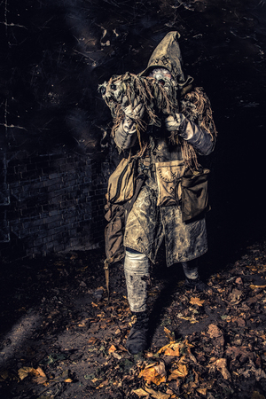 Post apocalyptic survivor, mysterious underground creature, stalker in gas mask and rags with runes, armed with handmade gun, hiding in dungeon, abandoned tunnel or city dark catacombs, sepia toned Zdjęcie Seryjne