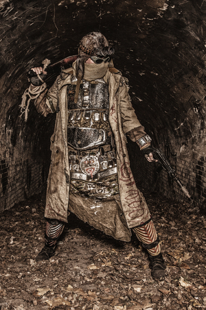 Survived in nuclear disaster and living in catacombs or city underground tunnels human creature, wearing rags and handmade lamellar body armor, hiding face behind mask, armed with pistol and machete