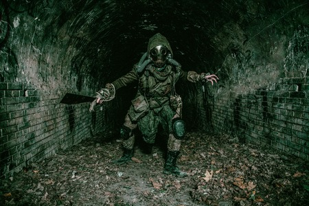 Post apocalyptic mutant creature or survivor in tatters and gas mask jumps out of darkness and attacking with handmade machete in abandoned tunnel, frightening dungeon or city old sewage collector Foto de archivo