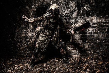 Post apocalyptic mutant creature or survivor in tatters and gas mask jumps out of darkness and attacking with handmade machete in abandoned tunnel, frightening dungeon or city old sewage collector Stock Photo
