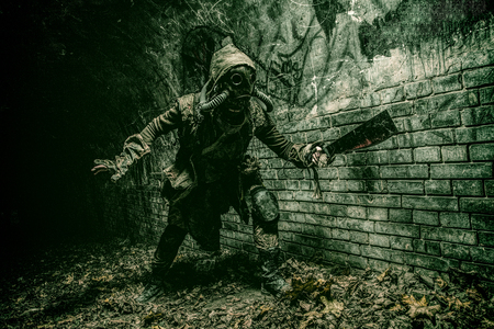 Post apocalyptic mutant creature or survivor in tatters and gas mask jumps out of darkness and attacking with handmade machete in abandoned tunnel, frightening dungeon or city old sewage collector Reklamní fotografie