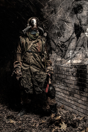 Survived in nuclear disaster or global ecological catastrophe human wearing rags, gas mask or air breathing apparatus and hiding in dark dungeon, catacombs or underground tunnel with handmade machete