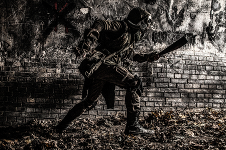 Post apocalyptic world survivor in gas mask, armed with handmade machete, running from darkness to light along dirty brick wall with graffiti. Stalker escaping from dangerous dungeon or city catacomb Stock Photo