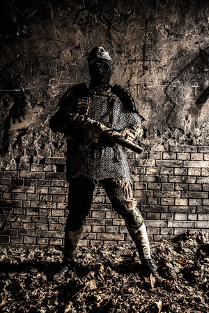 Post apocalyptic survivor, World War III soldier, global nuclear conflict partisan or stalker, in military cap and handmade body armor shooting with submachine gun wrapped in abandoned bunker or mine