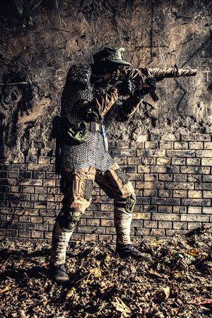 Post apocalyptic survivor, World War III soldier, global nuclear conflict partisan or stalker, in military cap and handmade body armor shooting with submachine gun wrapped in abandoned bunker or mine Stock Photo - 105913511