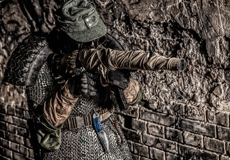 Post apocalyptic survivor, World War III soldier, global nuclear conflict partisan or stalker, in military cap and handmade body armor shooting with submachine gun wrapped in abandoned bunker or mine Reklamní fotografie - 105913513