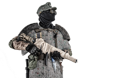 Nuclear post-apocalypse survivor, alternative history soldier or partisan in wool field cap, face mask, glasses and handmade armor, aiming submachine gun in camera studio shoot isolated on white