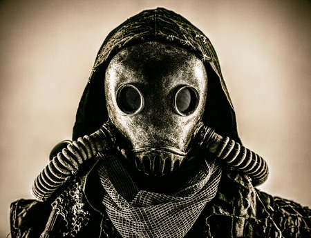 Close up portrait of nuclear post-apocalypse survivor, living underground mutant or creature, skilled stalker wearing rags and armored full-face gas mask or air breathing apparatus, toned shoot Reklamní fotografie - 105913688