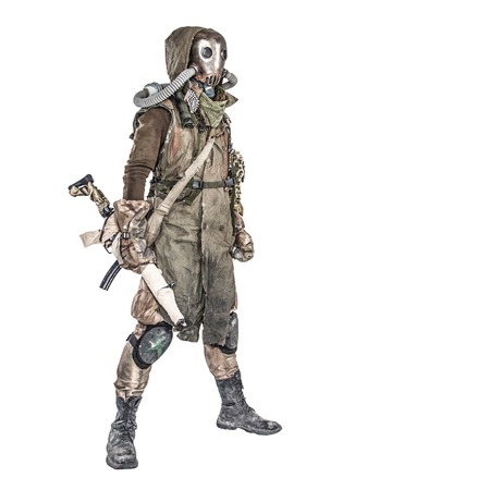 Survivor inhabitant of contaminated by nuclear catastrophe or dangerous chemical pollution world, in tatters and gas mask, standing with handmade firearm gun, isolated on white background studio shoot Reklamní fotografie - 105913690