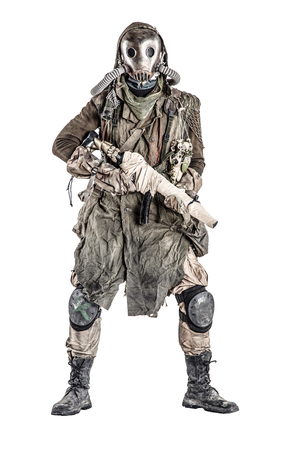 Survivor inhabitant of contaminated by nuclear catastrophe or dangerous chemical pollution world, in tatters and gas mask, standing with handmade firearm gun, isolated on white background studio shoot Reklamní fotografie