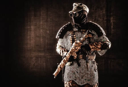Post apocalyptic soldier in black mask and glasses, wool field cap and handmade armor from car tires and hauberk, standing at attention with submachine gun on shoulder, black background studio shoot Stock Photo