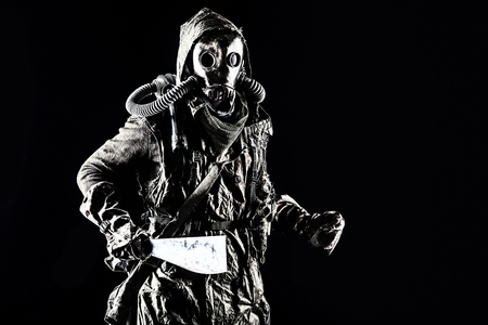 Low key portrait of post apocalyptic creature, living in catacombs mutant, survived in nuclear disaster human in ragged cloth and gas mask, armed with handmade cold weapon isolated on black background Reklamní fotografie - 105913759
