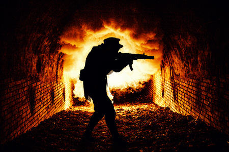 Silhouette of post apocalyptic soldier or survivor shooting with automatic firearm weapon in dark dungeon, city sewage tunnels, or underground bunker with explosion fire and smoke on background Stock Photo