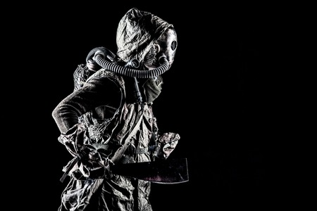 Low key portrait of post apocalyptic creature, living in catacombs mutant, survived in nuclear disaster human in ragged cloth and gas mask, armed with handmade cold weapon isolated on black background