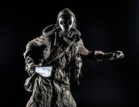 Low key portrait of post apocalyptic creature, living in catacombs mutant, survived in nuclear disaster human in ragged cloth and gas mask, armed with handmade cold weapon isolated on black background Reklamní fotografie - 105914117