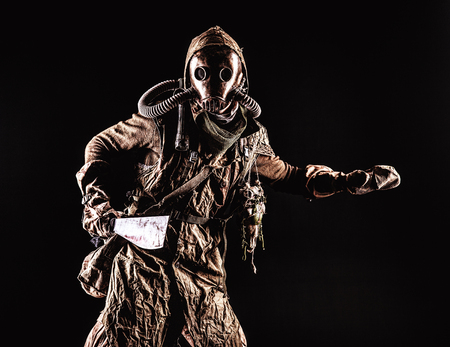 Low key portrait of post apocalyptic creature, living in catacombs mutant, survived in nuclear disaster human in ragged cloth and gas mask, armed with handmade cold weapon isolated on black background Reklamní fotografie - 105914120