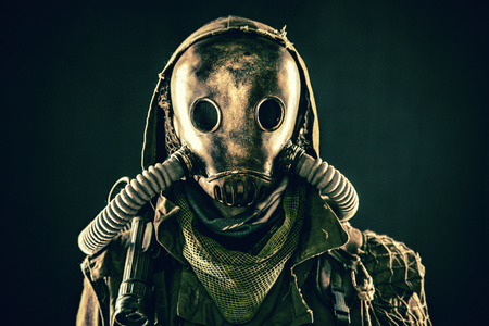 Close up portrait of nuclear post-apocalypse survivor, living underground mutant or creature, skilled stalker wearing rags and armored full-face gas mask or air breathing apparatus, toned shoot Reklamní fotografie - 105914122