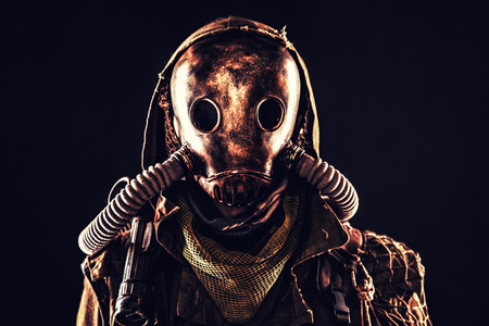 Close up portrait of nuclear post-apocalypse survivor, living underground mutant or creature, skilled stalker wearing rags and armored full-face gas mask or air breathing apparatus, toned shoot Reklamní fotografie - 105914123